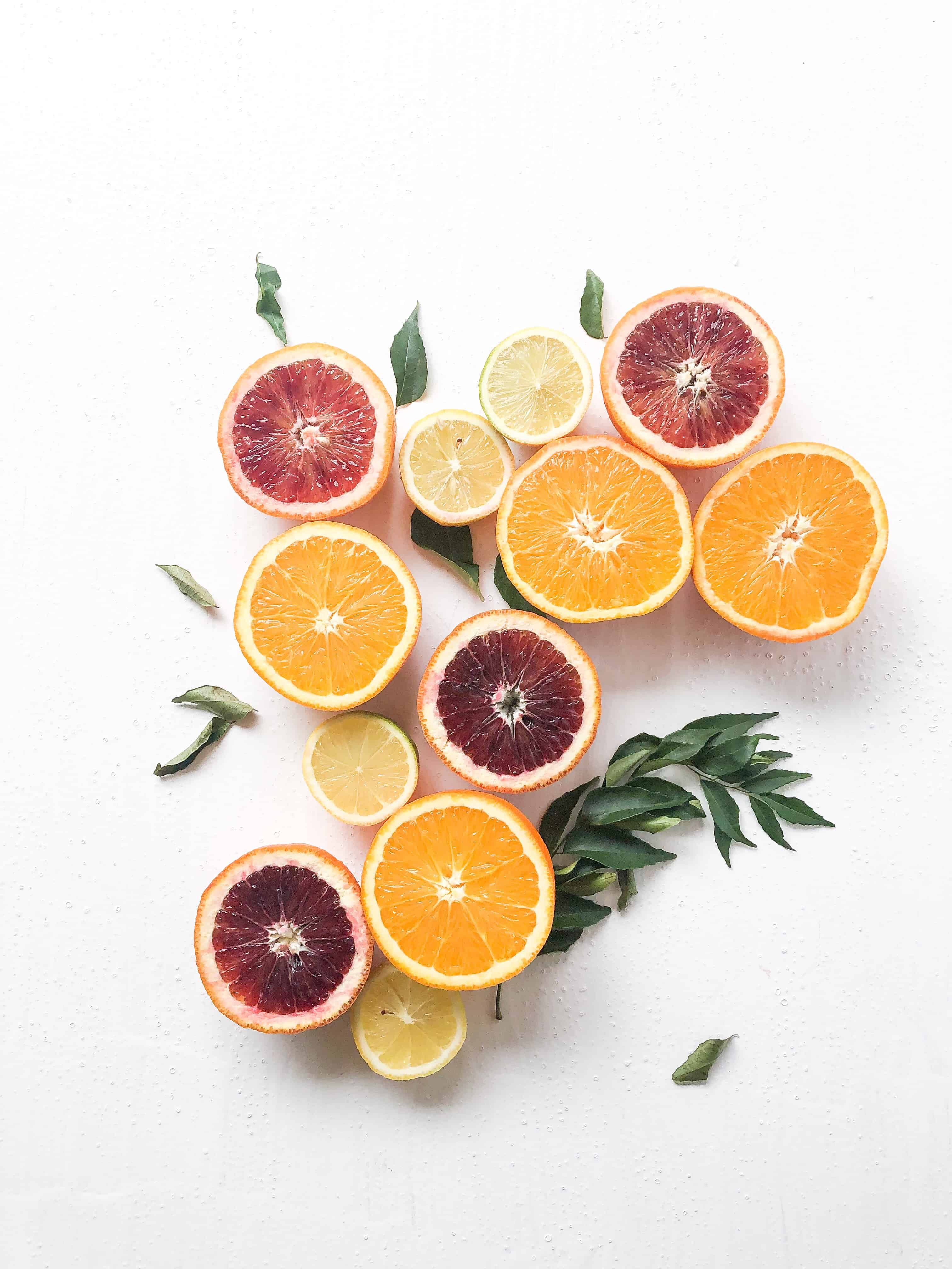 Oranges, blood oranges, and lemons with leaves on a white background