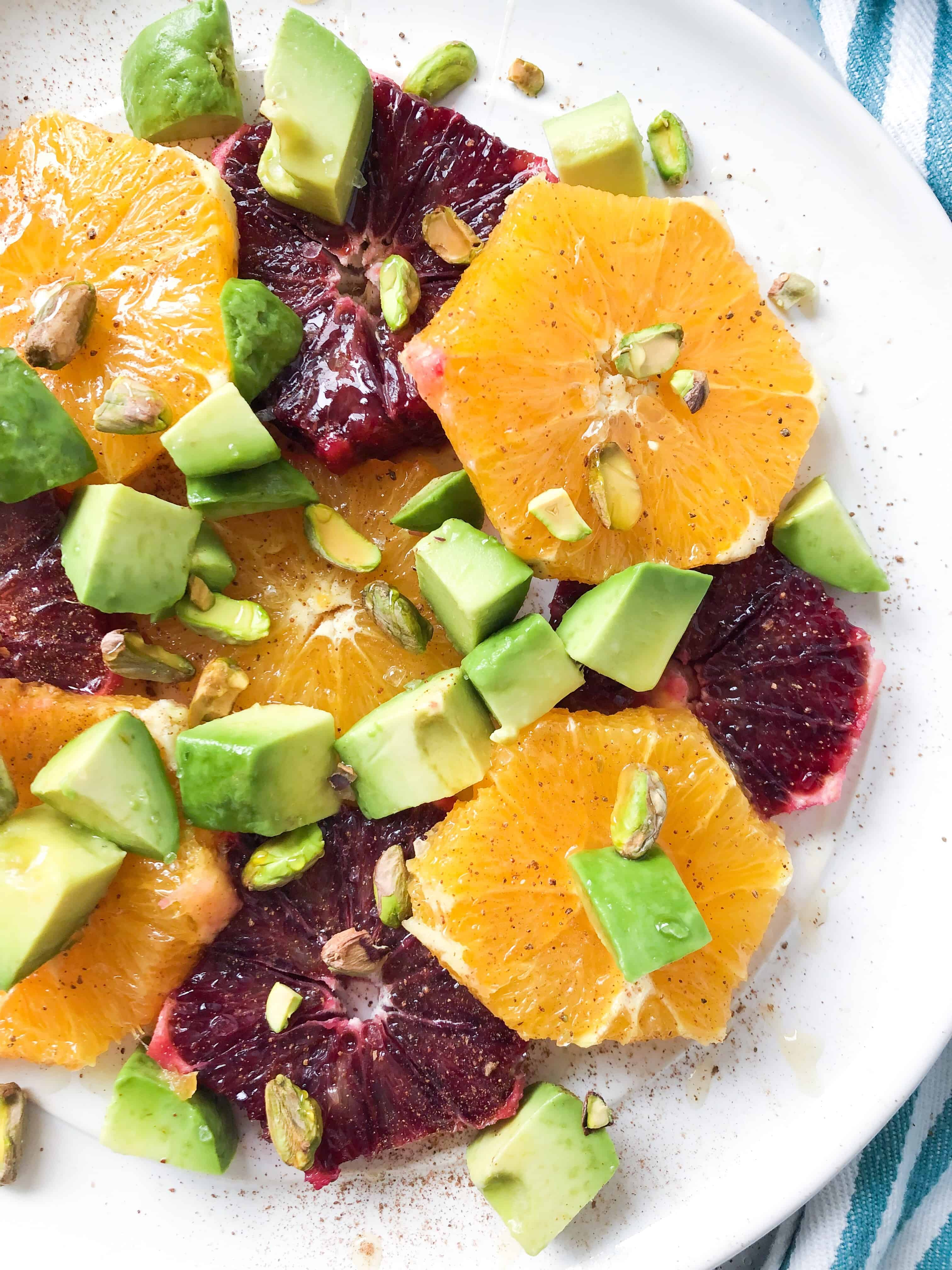 Oranges and blood oranges sliced on a plate with avocados, pistachios, and honey