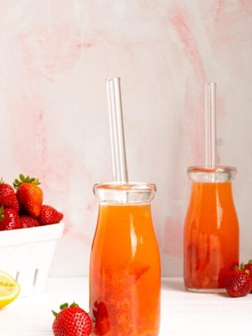 A bottle of strawberry lemonade with a straw