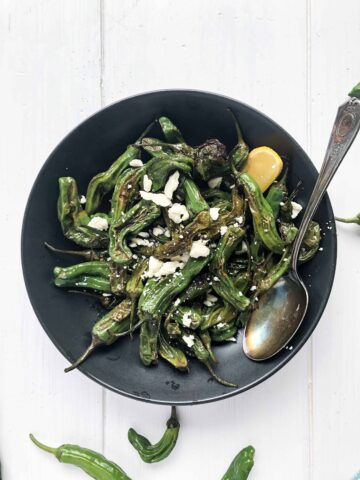 A bowl of blistered shishito peppers with lemon and feta