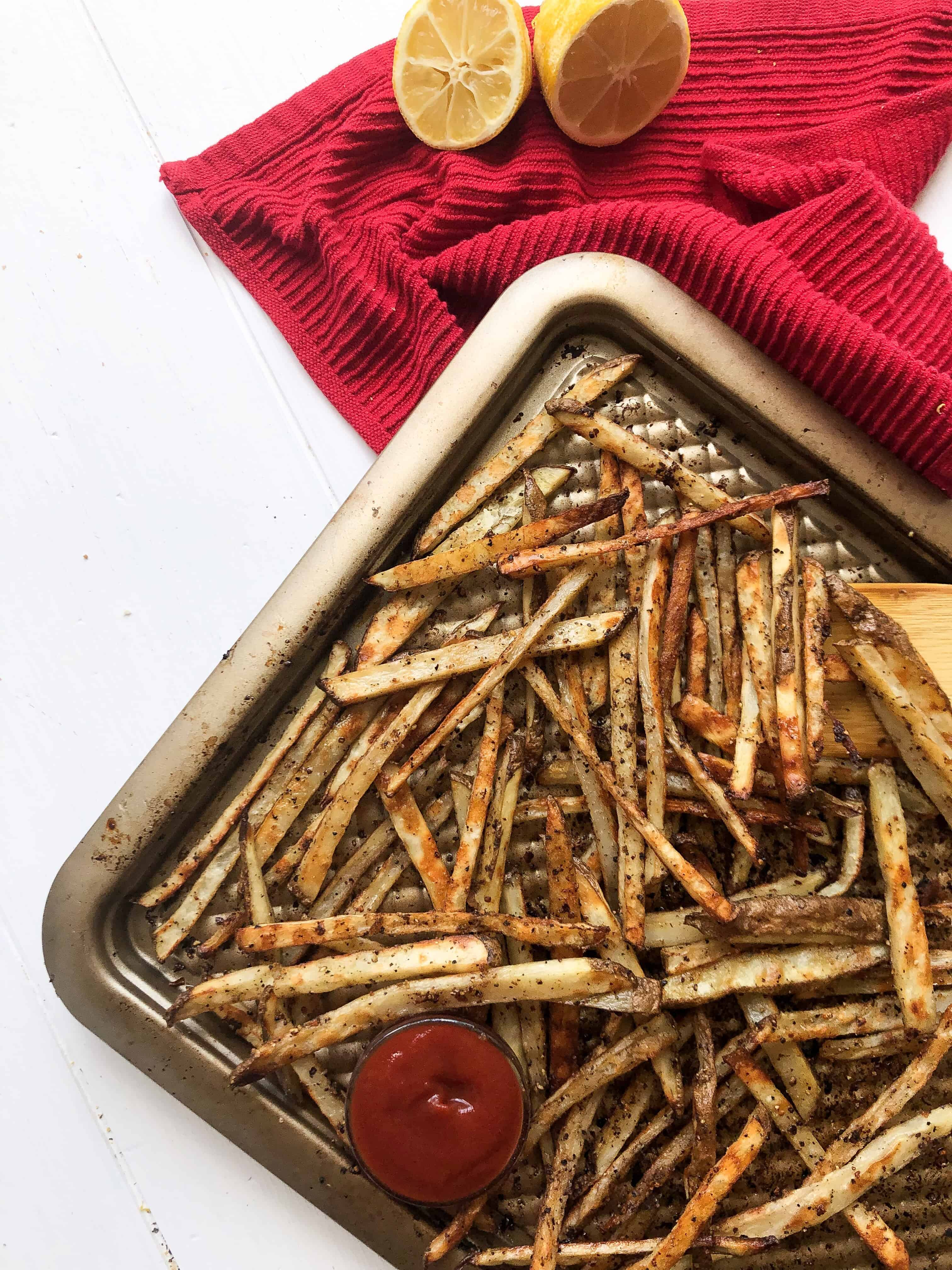 A sheet pan of lemon pepper fries with ketchup