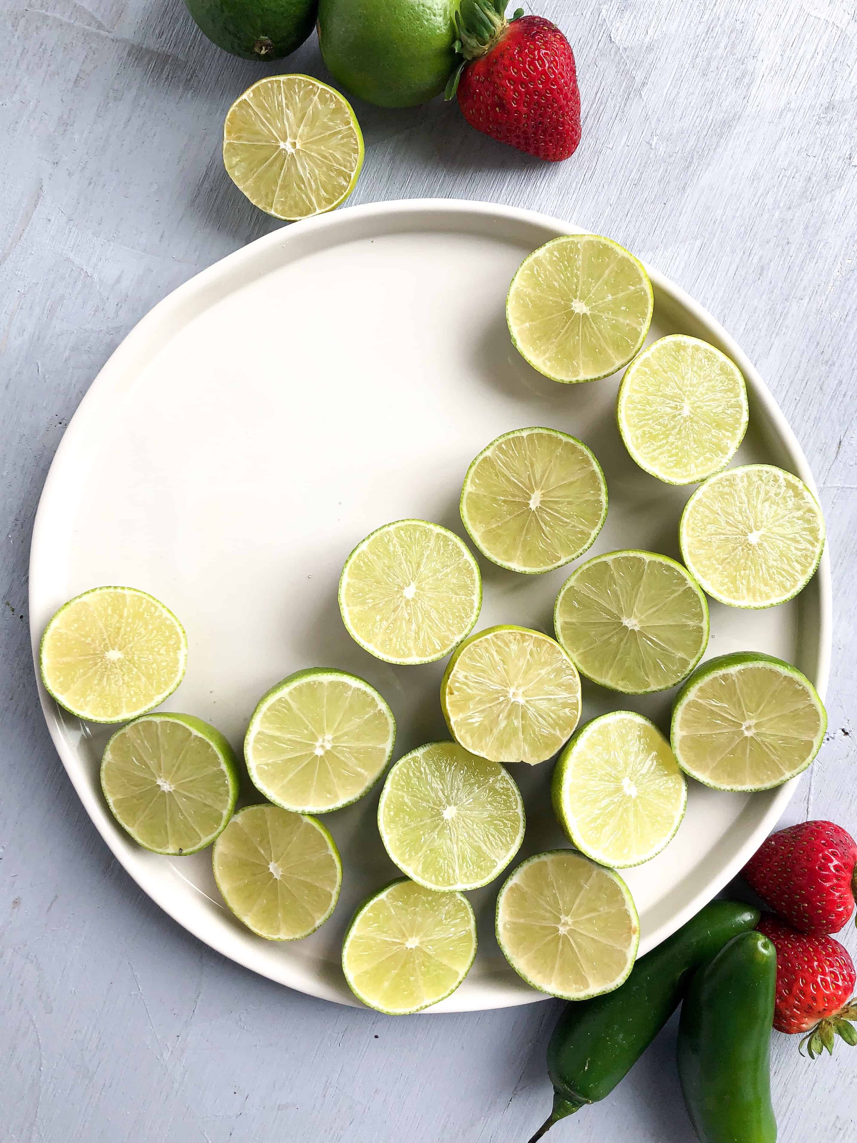 A plate of limes cut in half in a crescent shape