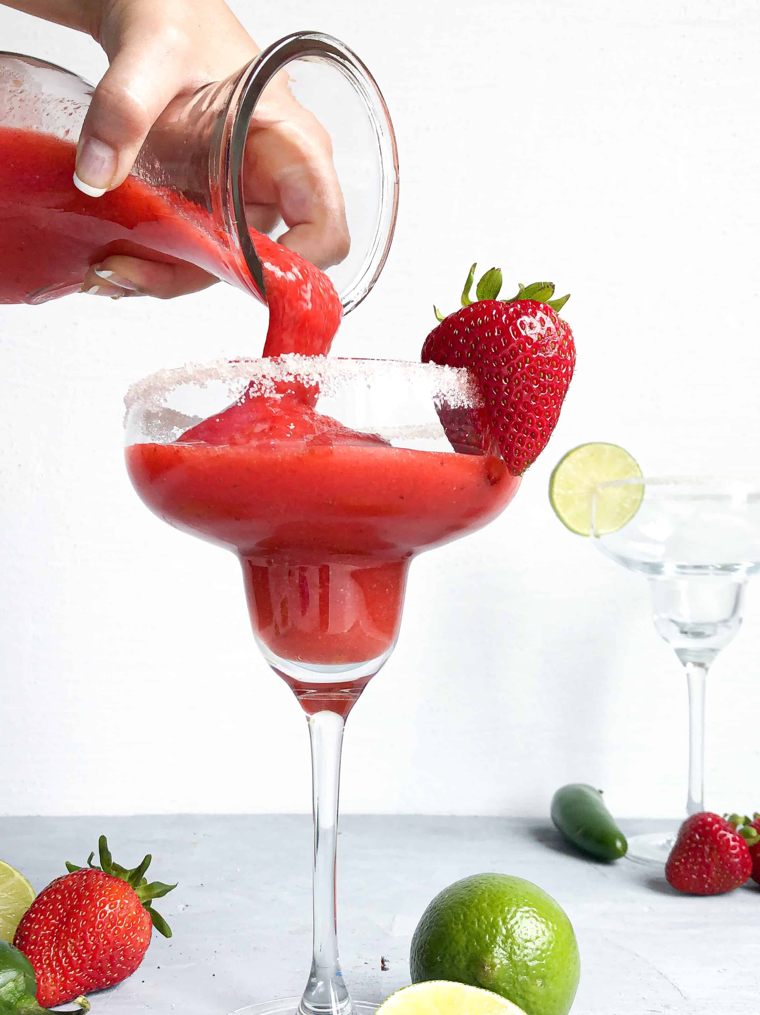 A pitcher pouring strawberry margarita into a glass