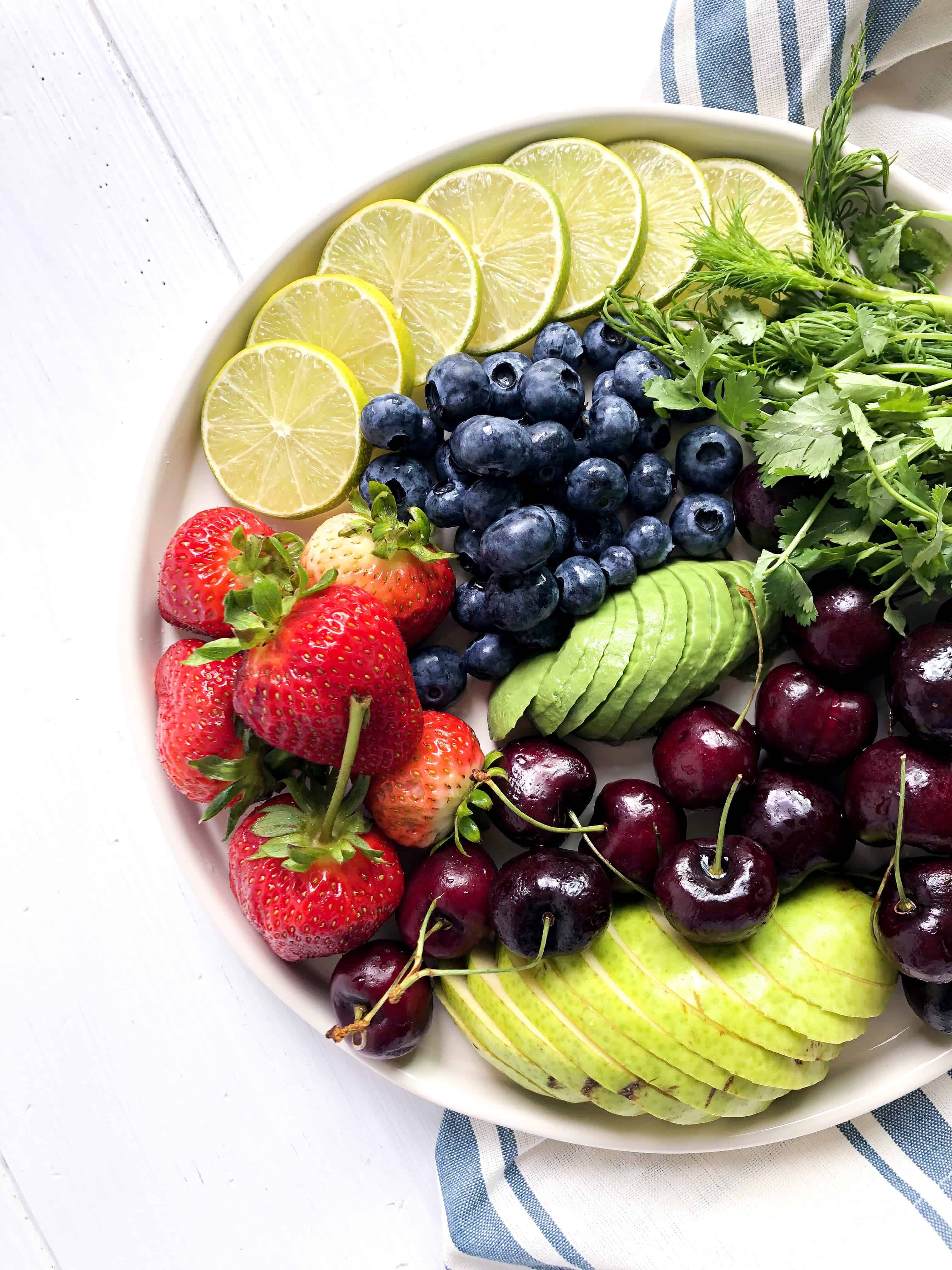 A plate full of freshly cut fruit and limes