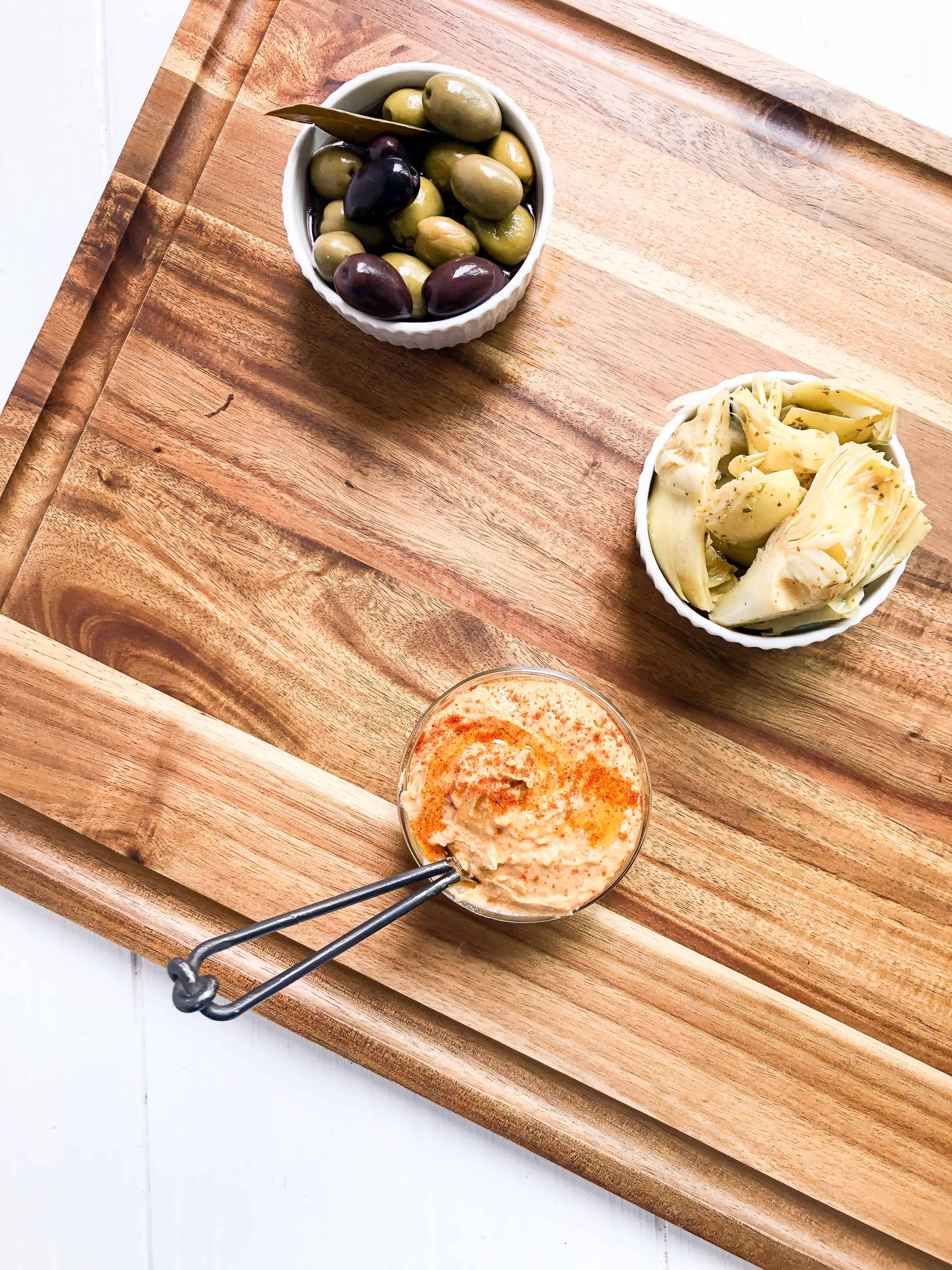 A cutting board with olives, hummus, and artichoke hearts