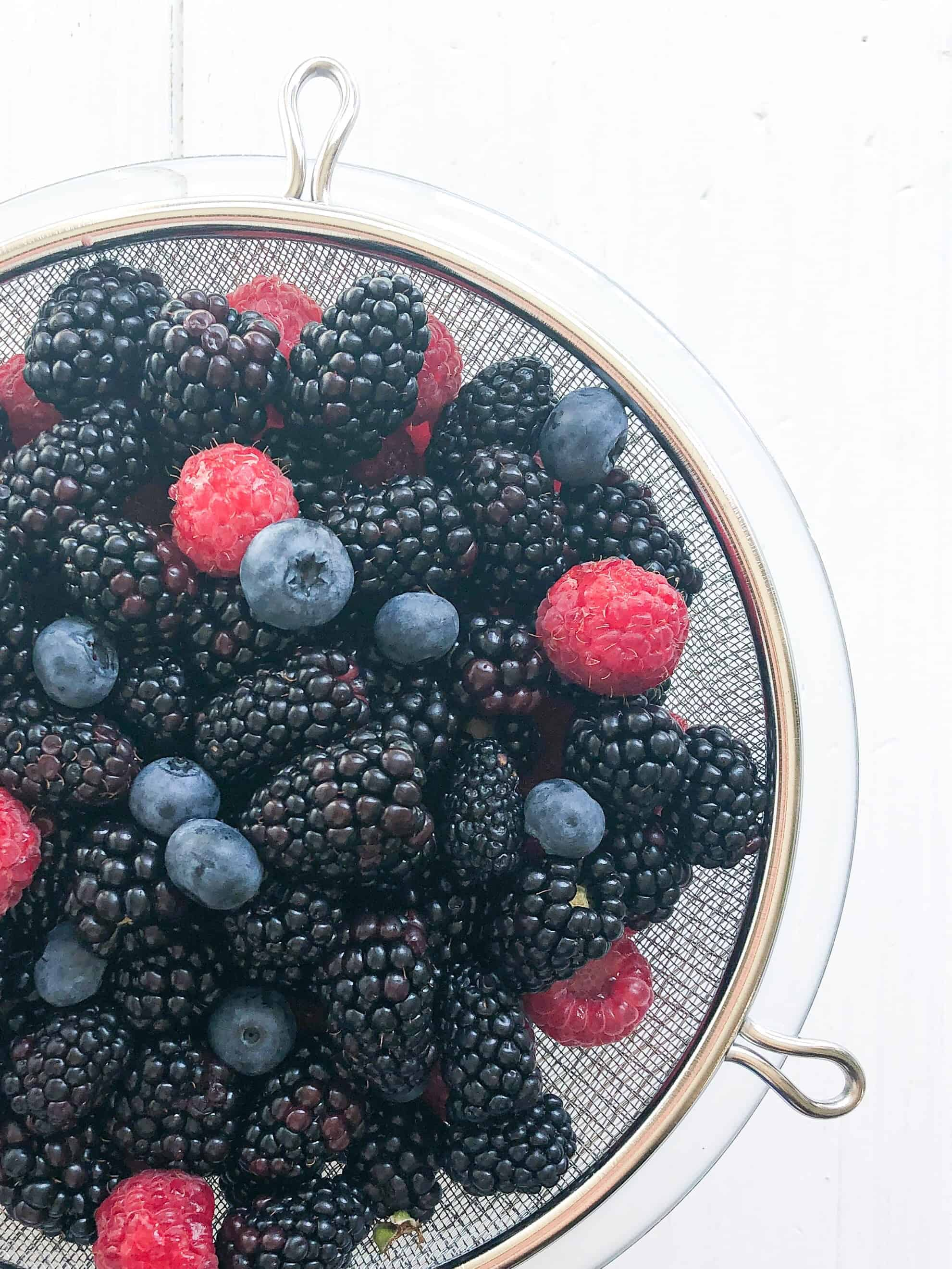 A bowl of fresh berries in a strainer
