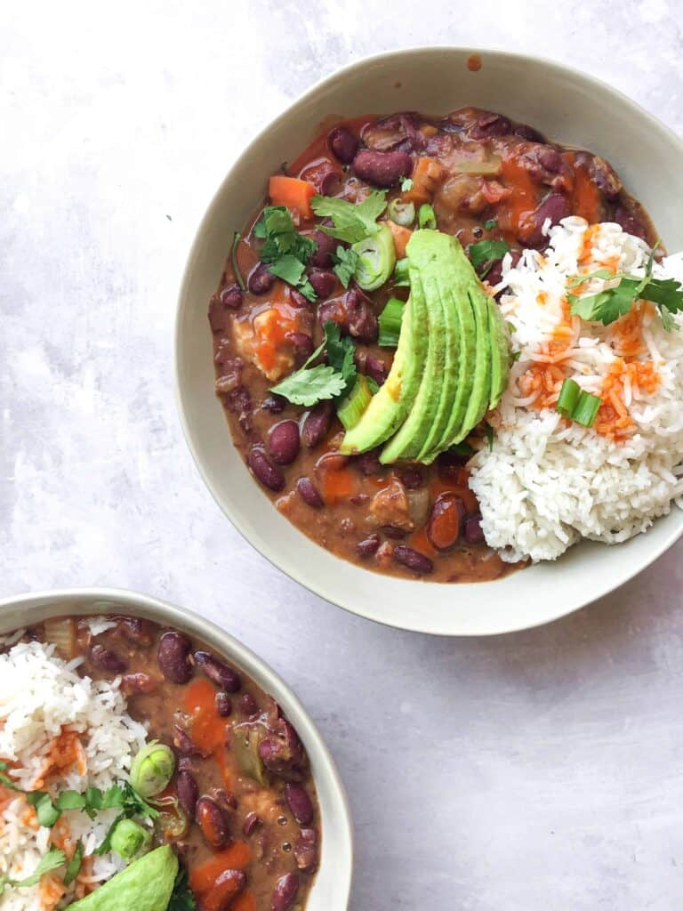 New Orleans Style Red Beans with Rice and avocado in two bowls.
