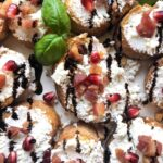 A plate of goat cheese pomegranate crostini with bread.