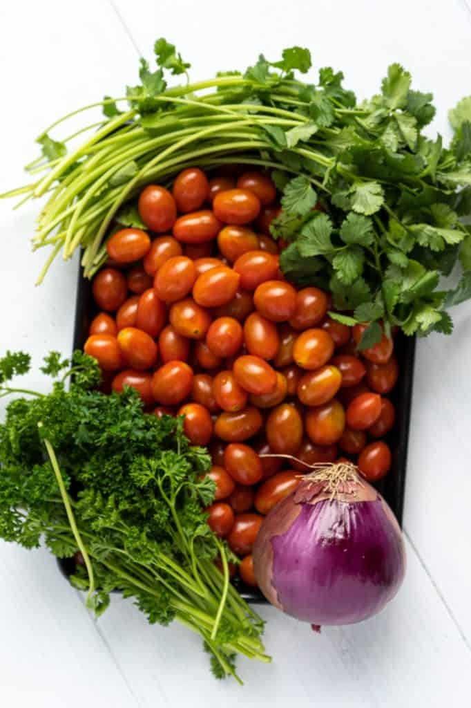 A bowl of tomatoes, onion and herbs for Classic Moroccan Tomato Salad.