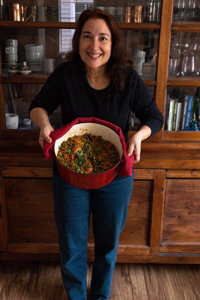 My mom holding a pot of arroz con pollo.