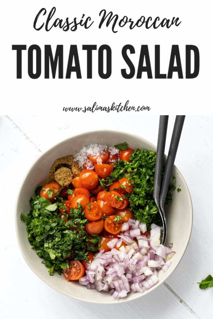 A bowl of tomato salad with onion and herbs.