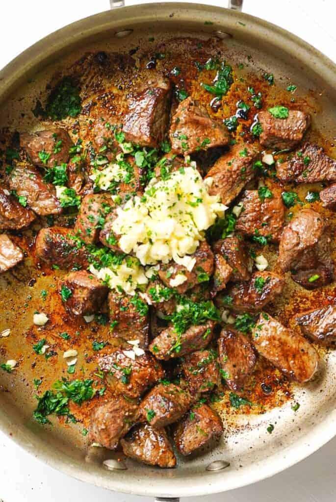 A frying pan full of Garlic Herb Steak Bites.
