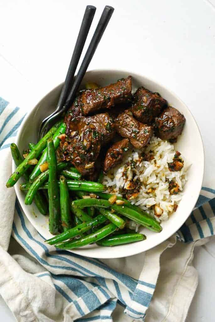 A bowl of Garlic Herb Steak Bites with green beans.