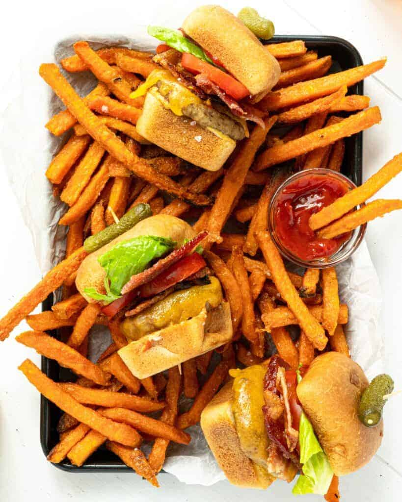 A tray of bacon cheeseburger sliders with fries.