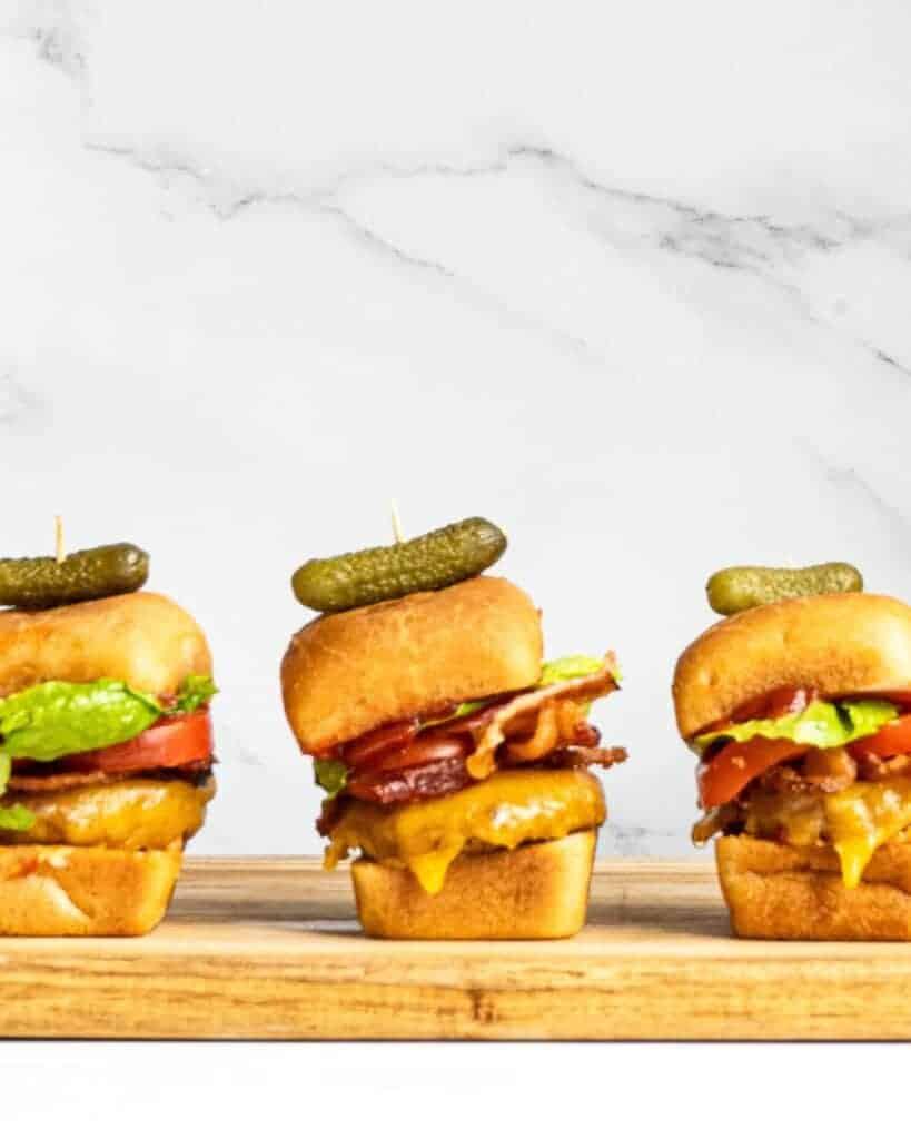 Three bacon cheeseburger sliders in a row.