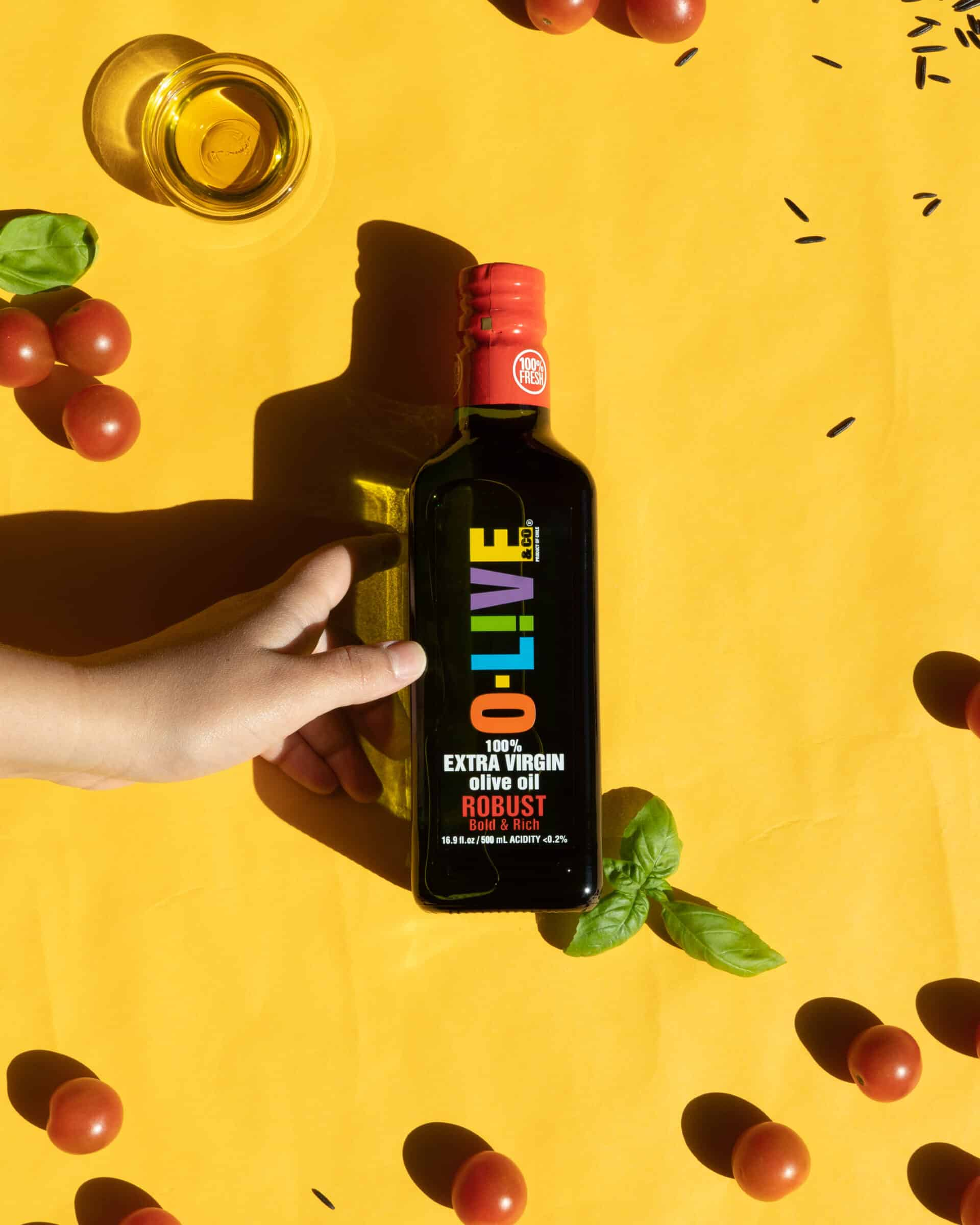 A bottle of olive oil on a yellow backdrop.