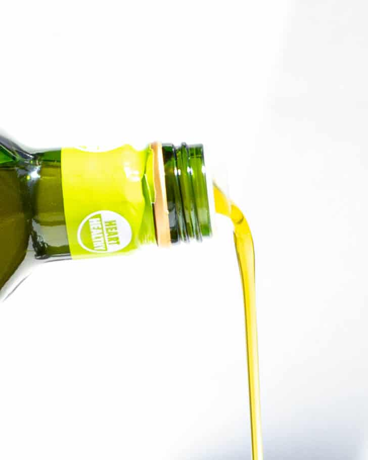 A bottle of olive oil drizzling.
