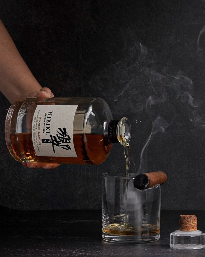 A bottle of Hibiki Suntory Whiskey pouring into a glass with a cigar.