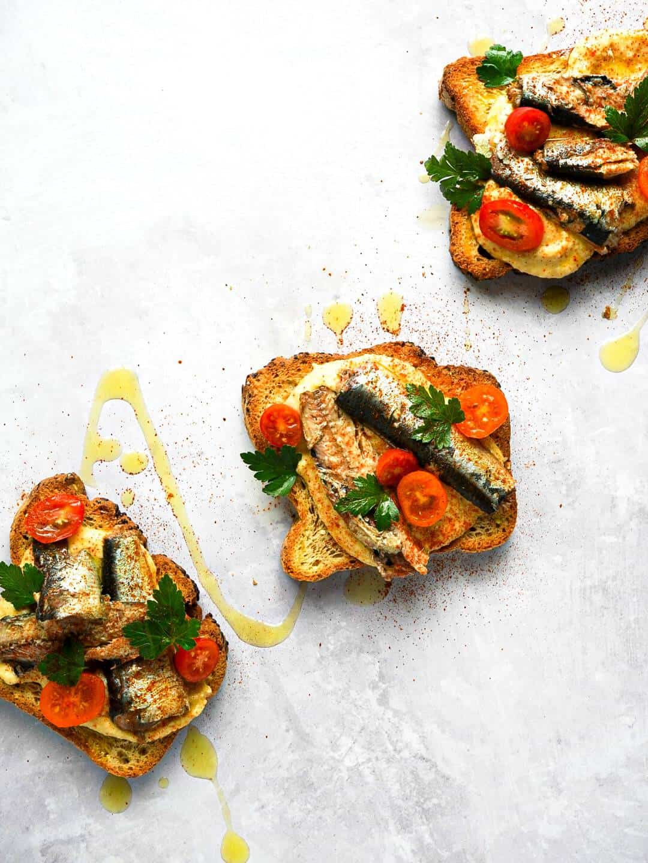 Three toasts with Wild Planet sardines on top.