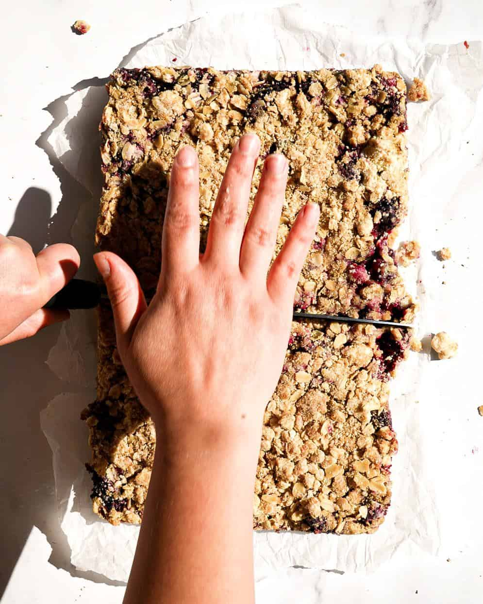 A hand holding a knife to cut blackberry crumb bars.