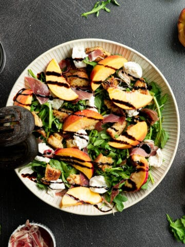 Burrata peach salad in a white bowl with salad spoons.