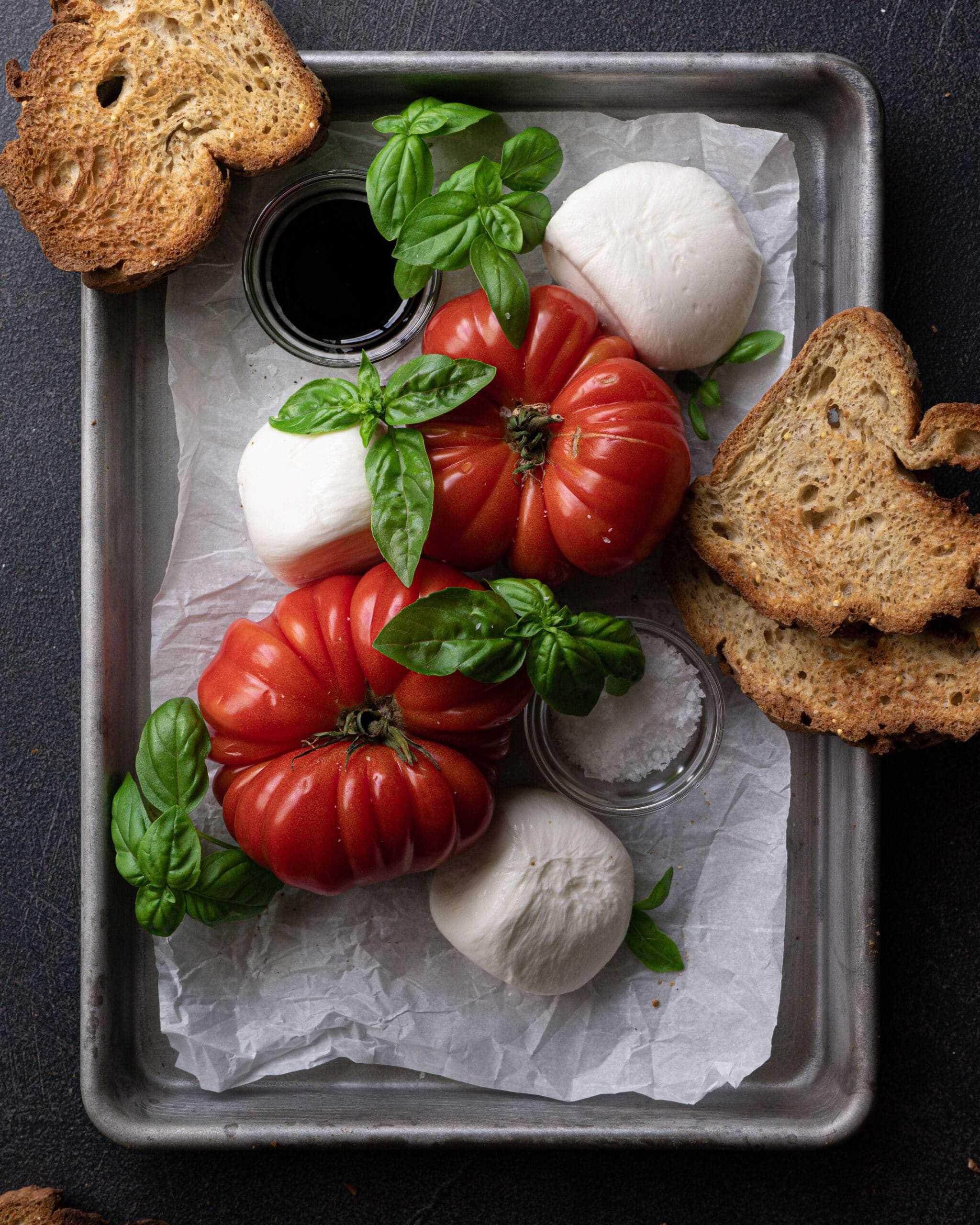 A sheet pan with heirloom tomatoes, burrata, basil, toast, balsamic glaze and salt.