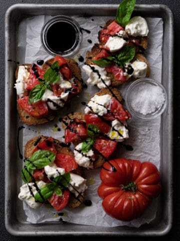 A sheet pan with Caprese crostini and a balsamic glaze.