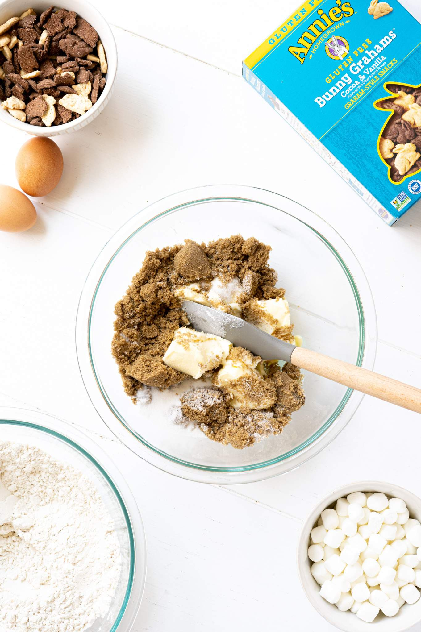 Butter and sugar in a mixing bowl with a spatula.