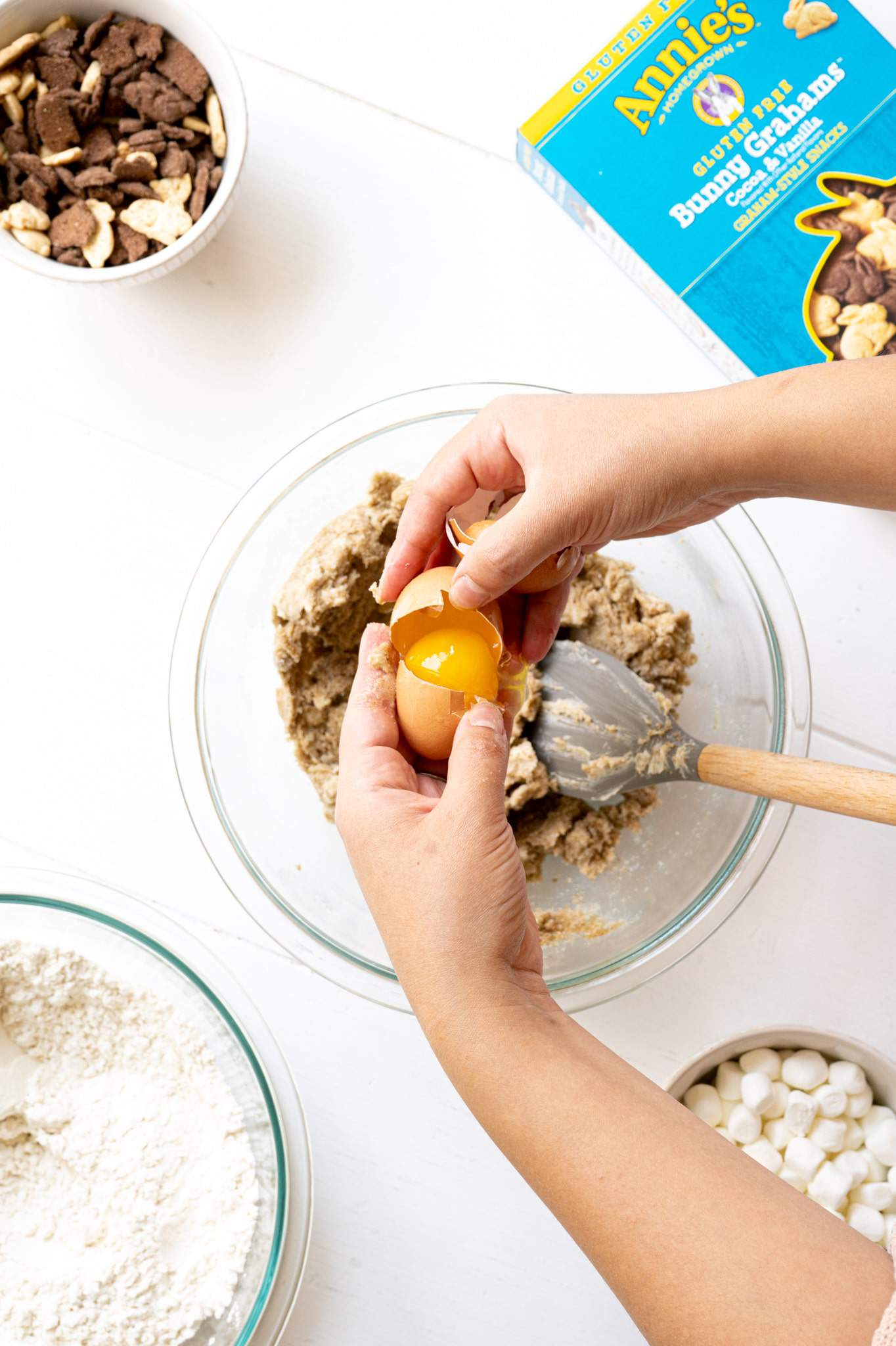Two hands cracking an egg into s'mores cookie dough.