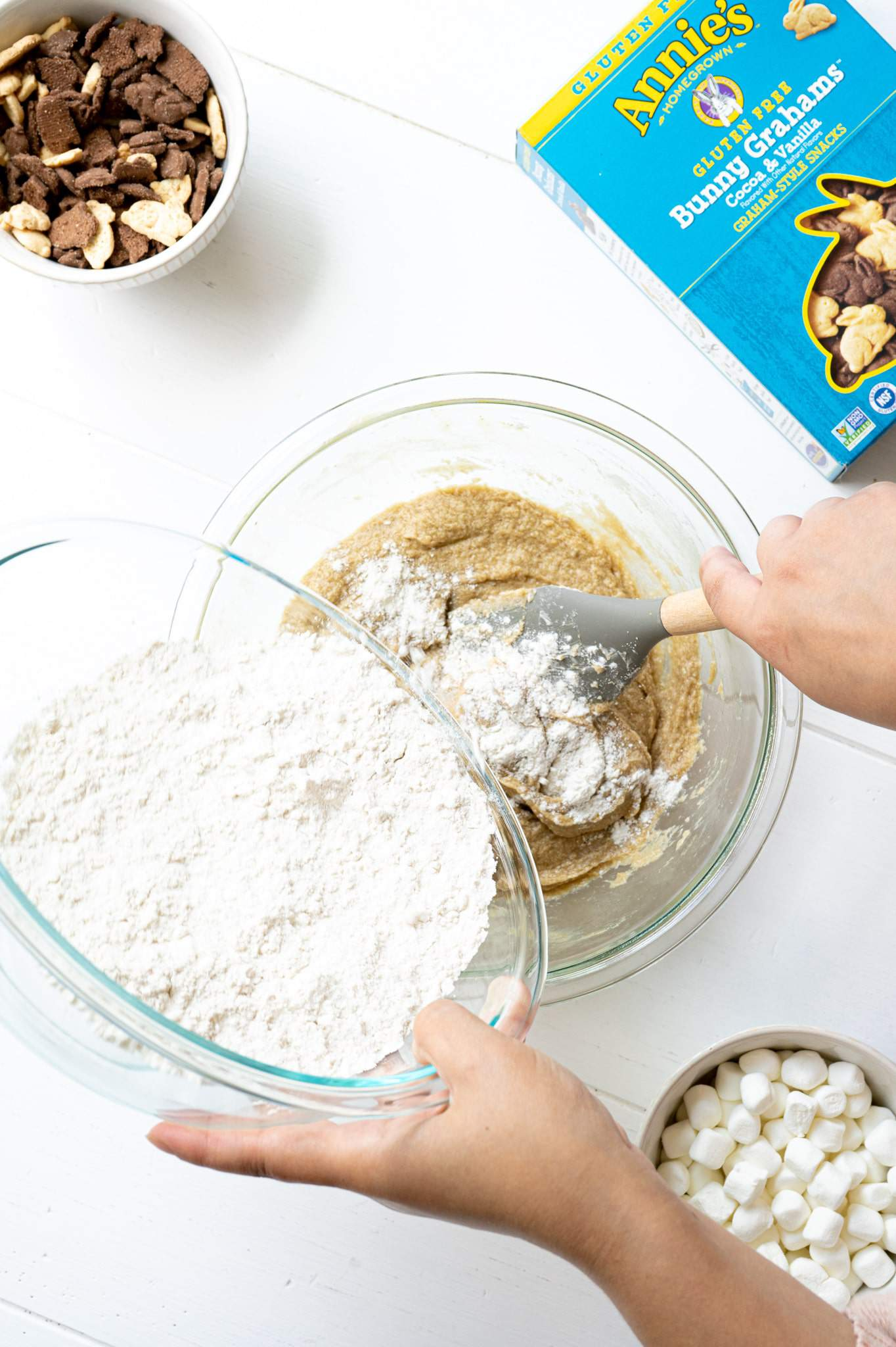 A hand pouring flour into a mixing bowl with butter, sugar, eggs and vanilla.