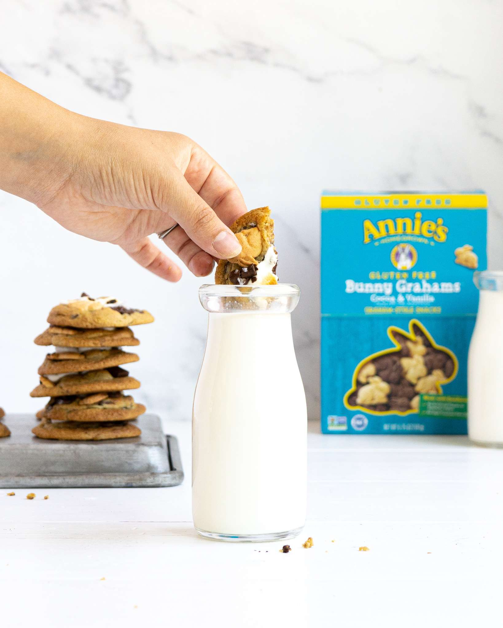 A s'mores cookie dipping into a jar of milk with an Annie's box in the background.