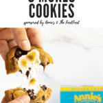 Two hands pulling apart a melty marshmallow s'mores cookie.