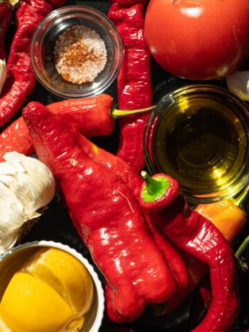 A tray of peppers, garlic, tomato, spices, oil and preserved lemons.