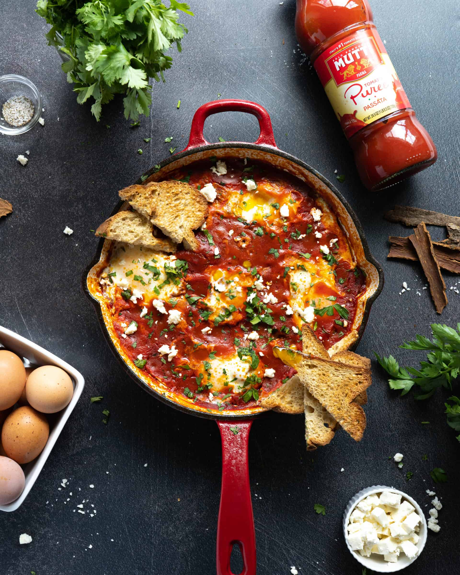 A pan of Moroccan shakshuka with slices of toast and meatballs.