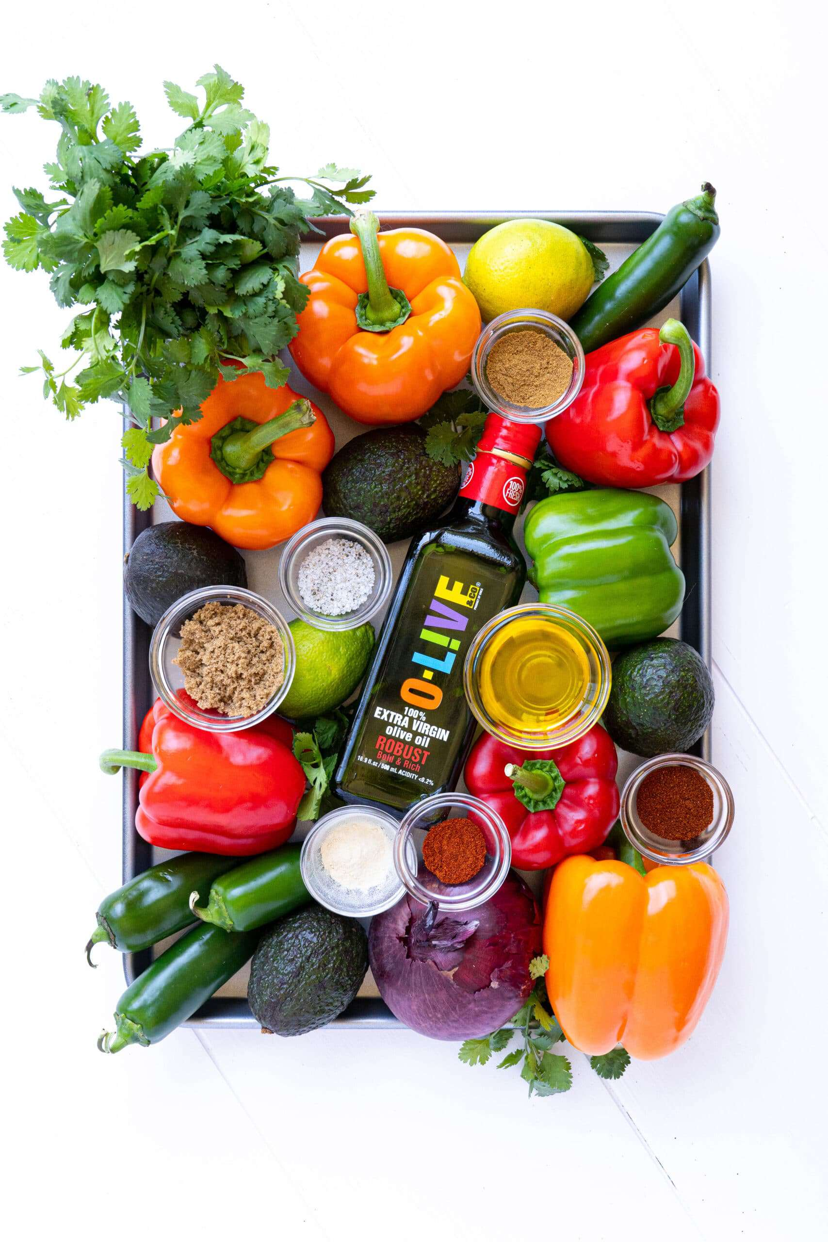 A sheet pan with veggies, spices and olive oil to make fajitas.