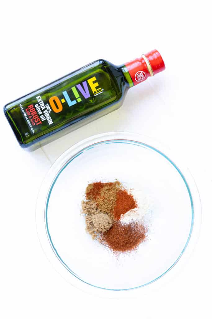 A spice rub in a bowl and a bottle of olive oil.