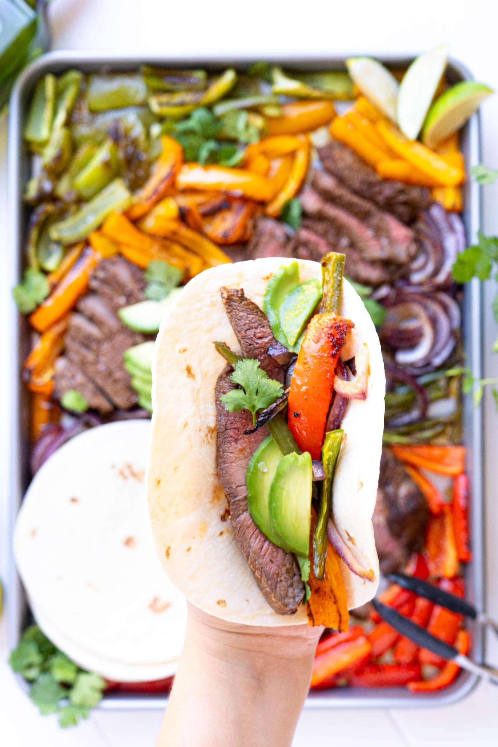 A hand holding a steak fajita over a sheet pan full of fajita ingredients.