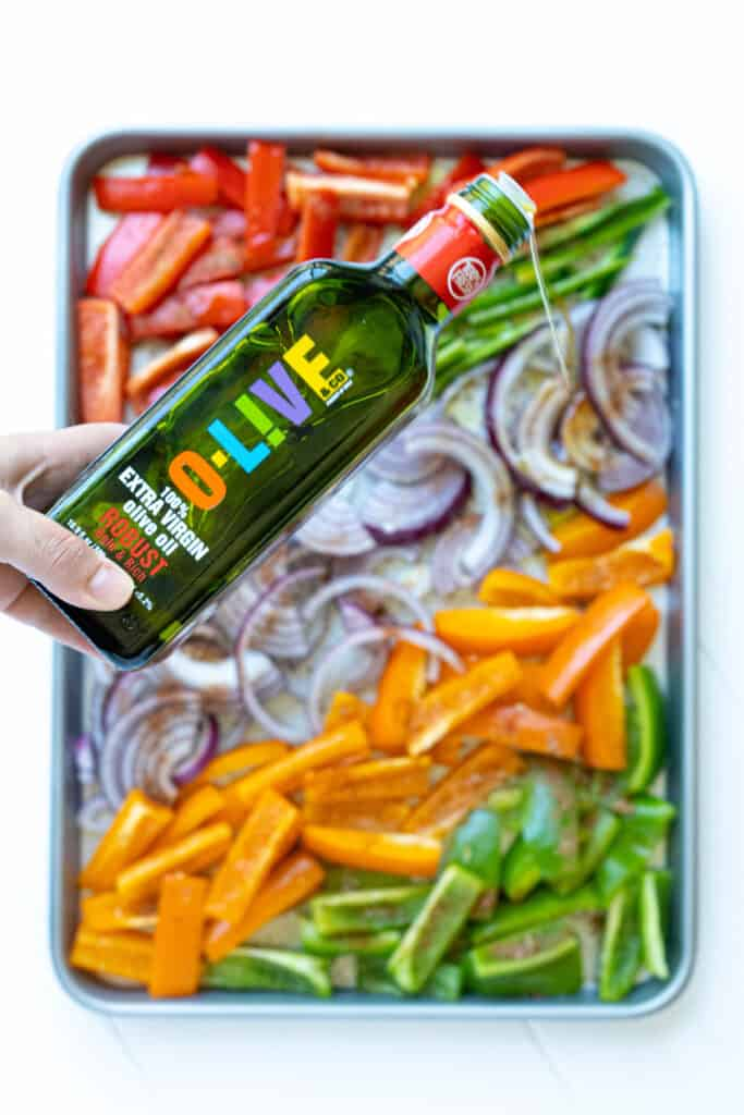 A bottle of olive oil pouring onto a sheet pan of peppers and onions.
