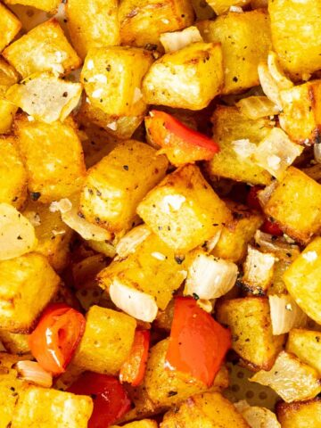 A close up of home fries with onion and peppers.