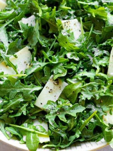 A white bowl with arugula and shaved parmesan.