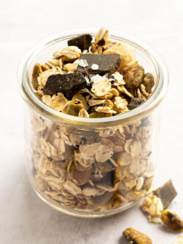 Granola in a glass jar with chocolate chunks and flakey salt.