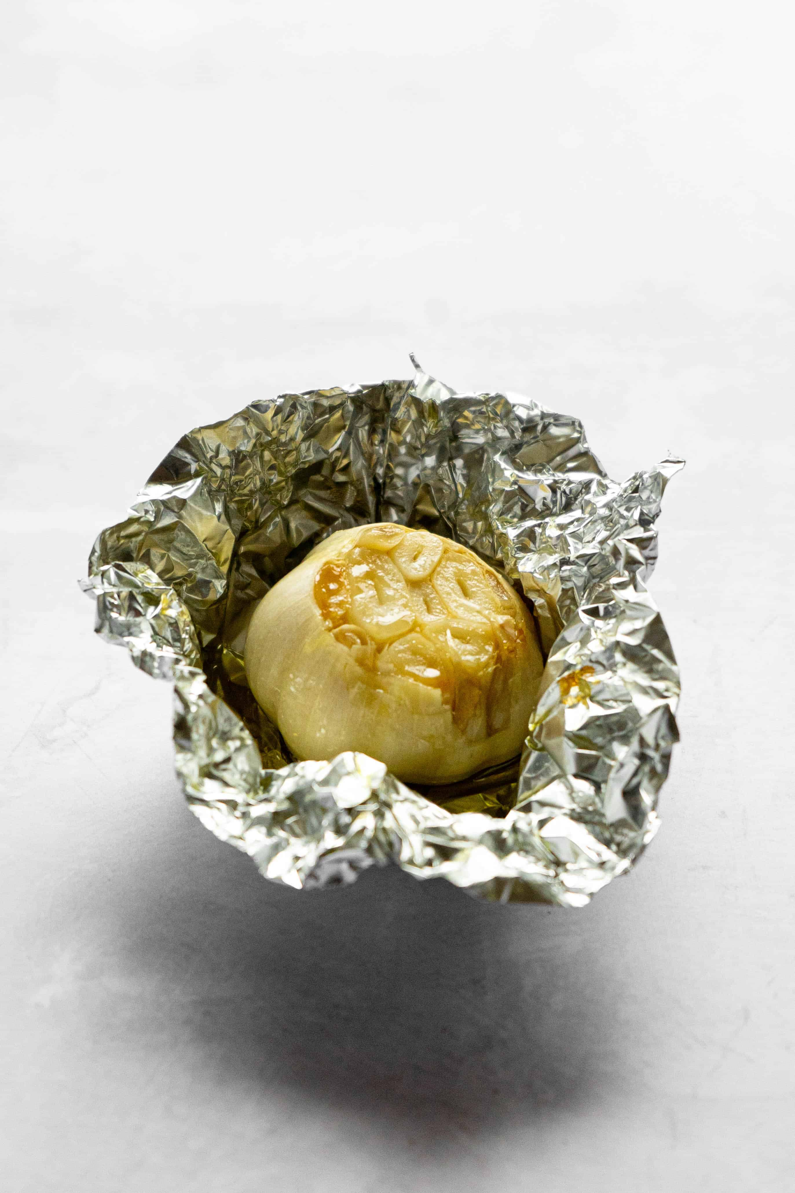 An aluminum foil pouch with roasted garlic and olive oil.