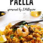 A plate full of seafood paella with shrimp and mussels.