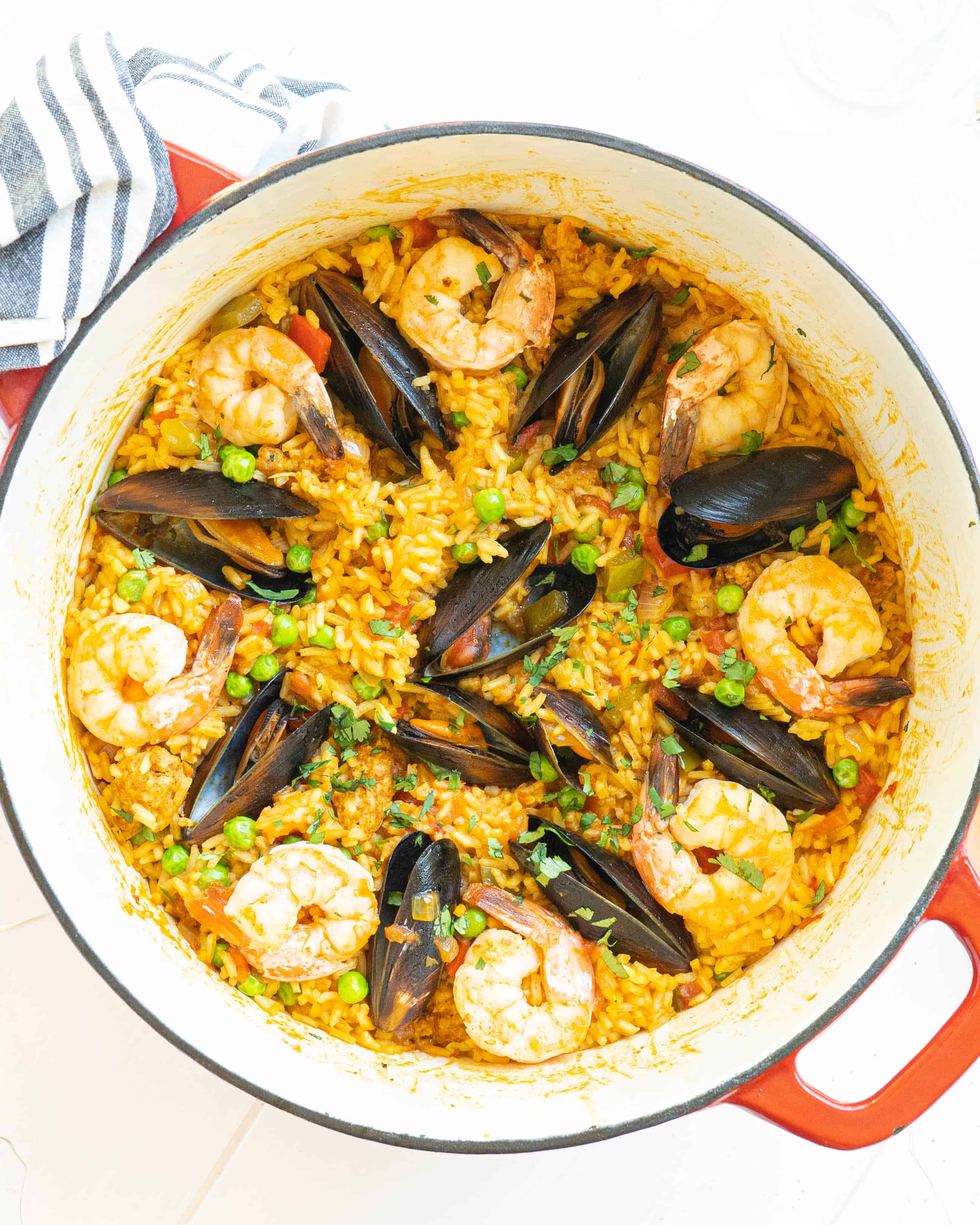 A pot full of seafood paella topped with mussels and shrimp