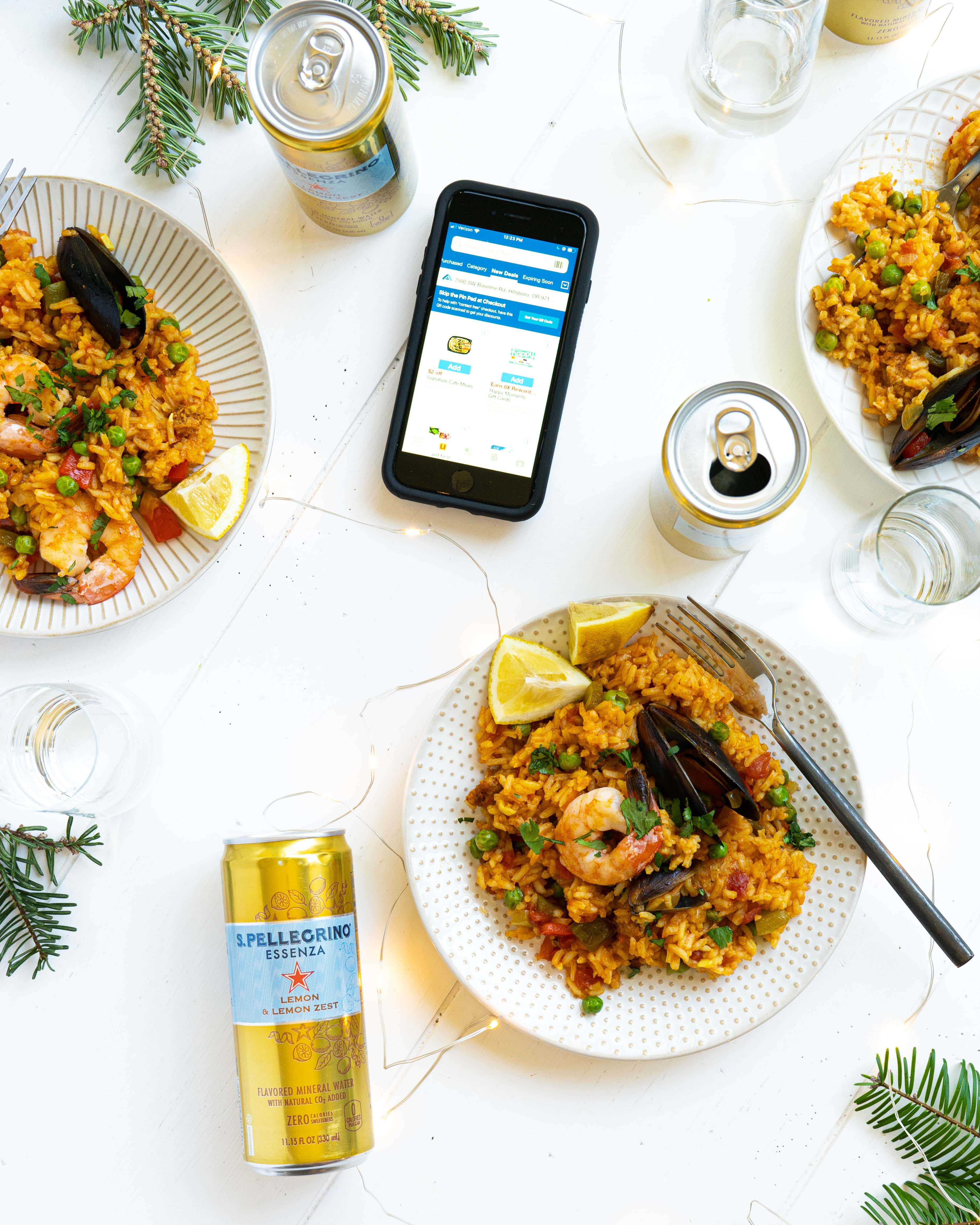 Plates of seafood paella next to cans, glasses and a phone