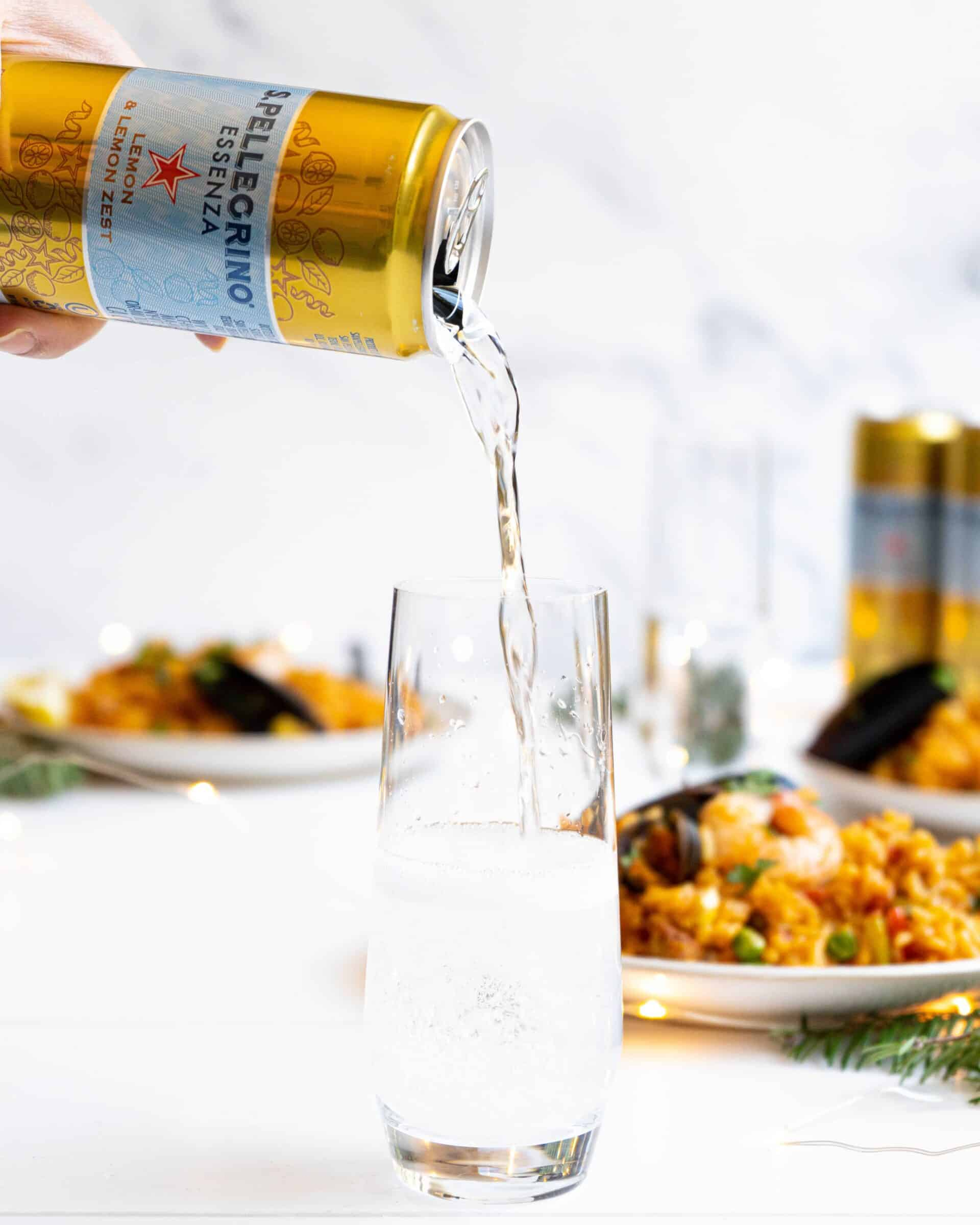 A can of S.Pellegrino pouring into a stemless glass amongst seafood paella