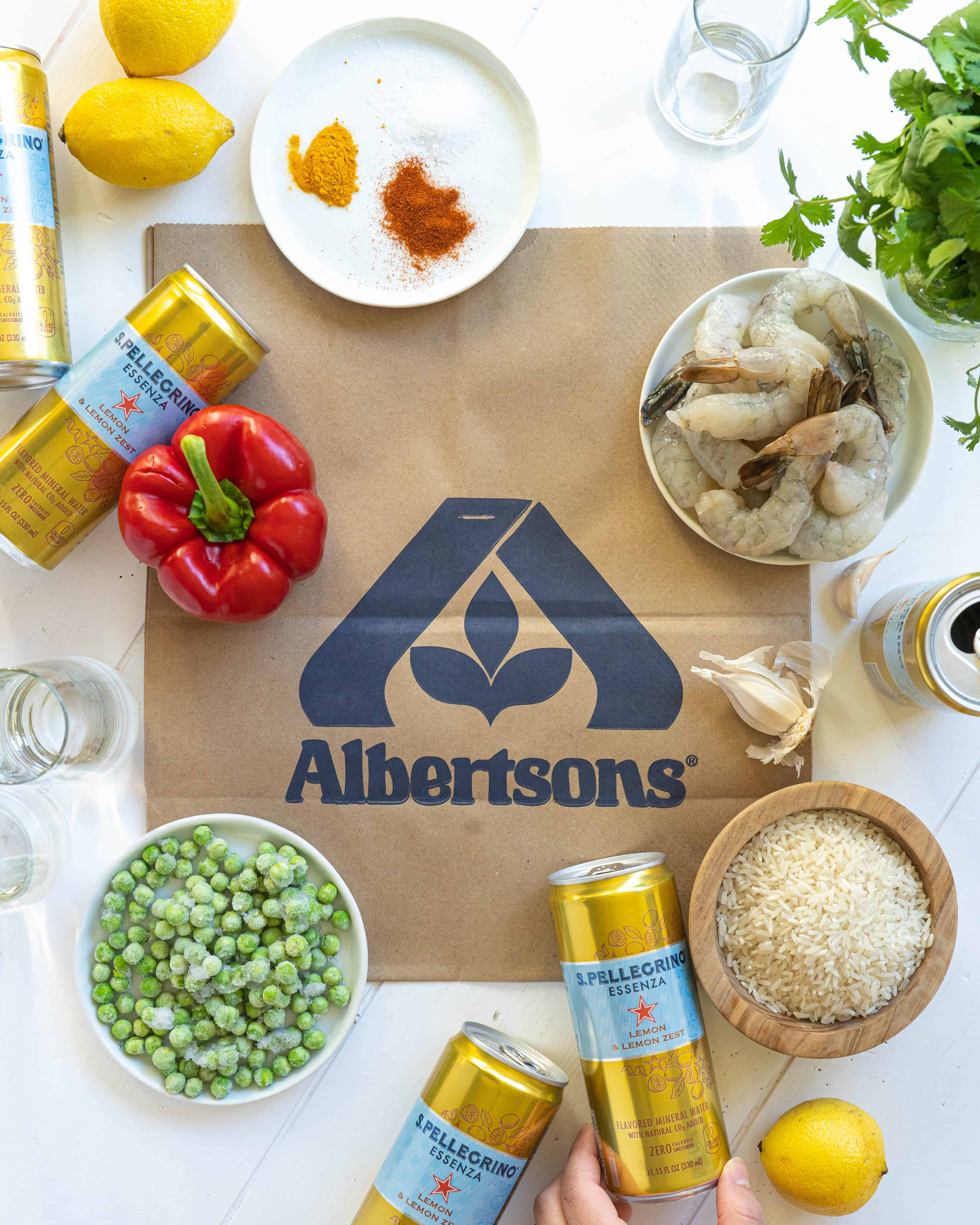 Ingredients on an Albertsons bag with cans of mineral water and glasses