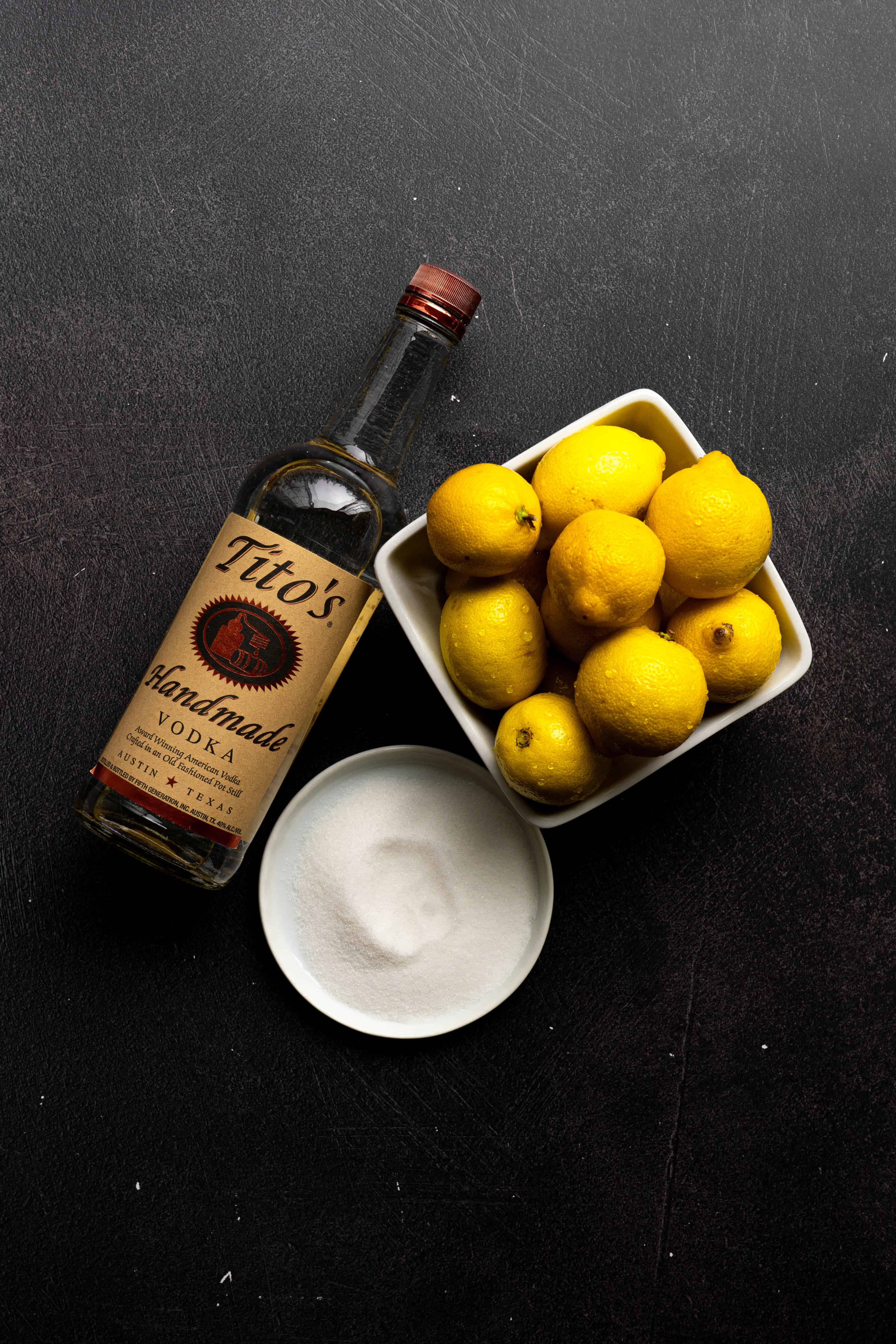 A bottle of vodka, a bowl of lemons and a bowl of sugar