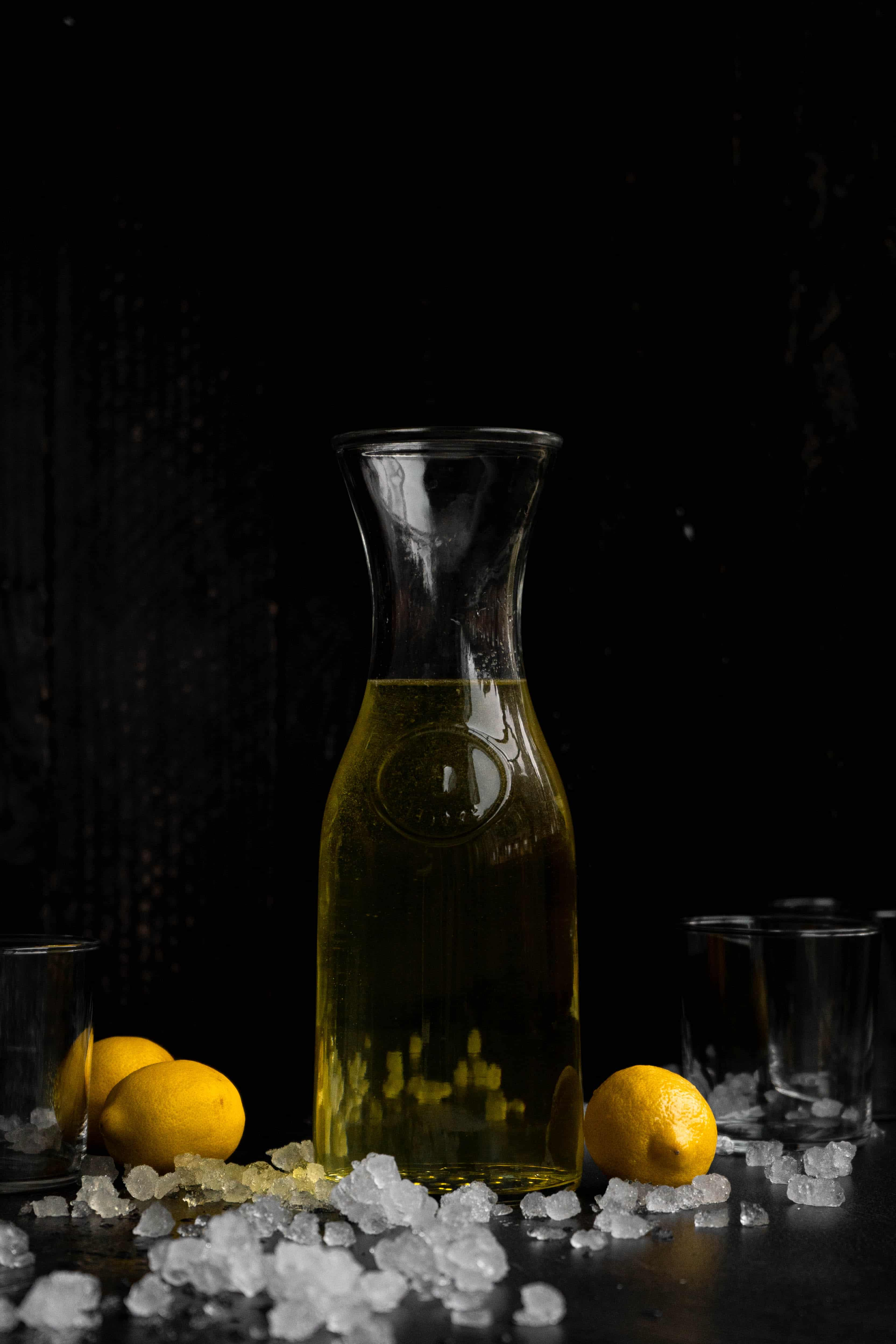 A bottle of limoncello amongst ice and lemons