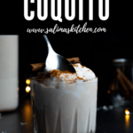 A hand holding a spoon scooping some coquito out of a glass